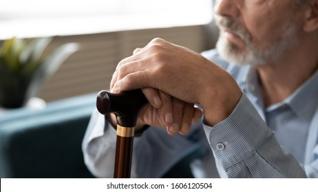 Horizontal view elderly 60s hoary man sitting on couch close up focus on hands holding stick cane, concept of senile diseases causing walking disorders, health problems, disabled person, nursing home