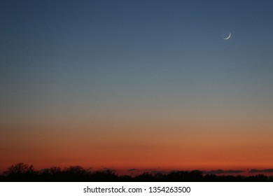 Horizontal view of the evening sky showing a range of color, from blue above to orange along the horizon. Featuring the moon on the right with most in shadow and only a sliver of crescent in light.