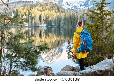 Horizontal view of female tourist enjoys tranquil remote mountain lake view, stands back to camera, carries big blue rucksack, wears raincoat and rubber boots, stands near green firs on stones