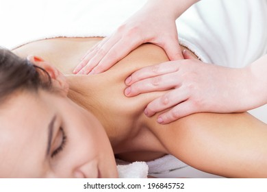 Horizontal view of hands massaging female neck