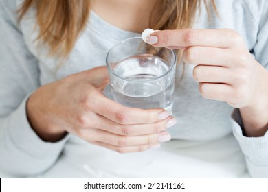 Horizontal view of ill woman taking aspirin