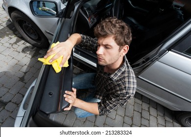 Horizontal view of man cleaning a car