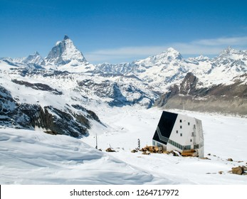 horizontal view of the Monte Rosa mountain hut with the famous Matterhorn peak and surrounding winter landscape in the background