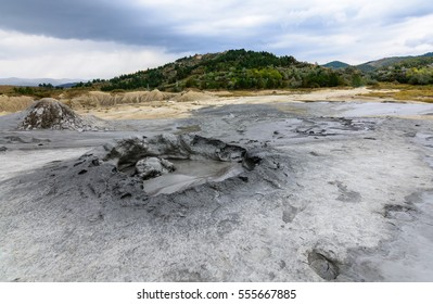 Horizontal view with muddy volcano closeup. Natural park with muddy volcanoes, dramatic landscape, unique geological phenomenon in Europe and beautiful sky above.