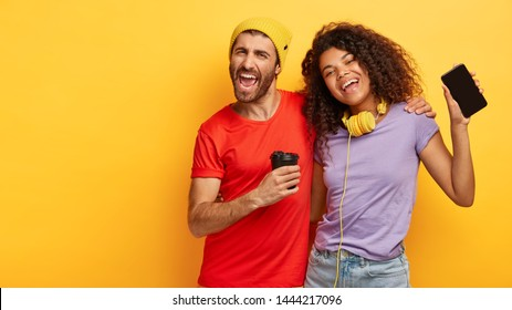 Horizontal view of playful positive mixed race couple cuddle and sing happily, boost energy and mood with cool music on smartphone, drink fresh coffee, look upbeat and entertained, isolated on yellow