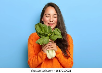 Horizontal view of pleased Korean woman holds freshly leafy vegetable, enjoys eating nutrient food containing vitamins, keeps eyes closed with pleasure, wears orange sweater, isolated on blue wall