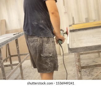 Horizontal view of a professionally dressed carpenter varnishing a board