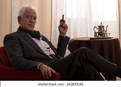Horizontal view of senior millionaire smoking cigar