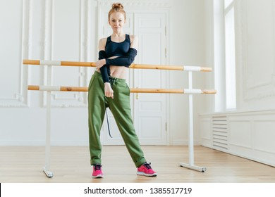 Horizontal view of slim female dancer wears black top and green sport trousers, stands in hall, has finger hair combed in bun trains all day ballet bare in background. Young fit gymnast has stretching