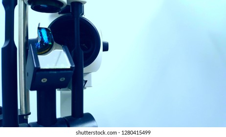 Horizontal view of slit lamp and tonometer on blue wash background