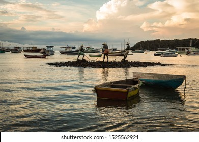 Horizontal view of Three fishermen (Tres pescadores) sculpture and boats at Buzios, Brazil during dusk on a cloudy summer day.  Beach became famous after being visited by movie star Brigitte Bardot