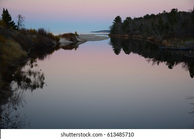 A horizontal view of a very calm river at sunset. The mouth of the Two Hearted River in the Upper Peninsula of Michigan.