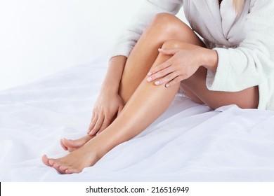 Horizontal view of woman using body lotion