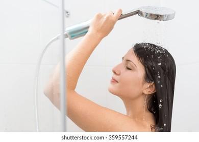 Horizontal view of woman using hand shower