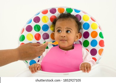 Horizontal waist up shot of a baby girl in highchair being fed by a spoon by her mother.