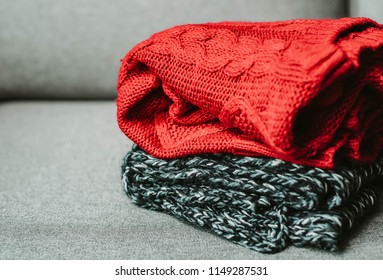 horizontal, warm sweaters on grey couch, seasonal concept, autumn fall winter outfit, cold weather, huggy