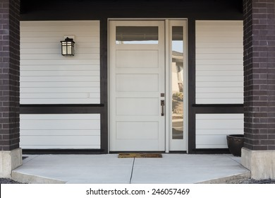 Horizontal of White And Black Front Entryway with White Siding, a White Front Door, and Black Framing