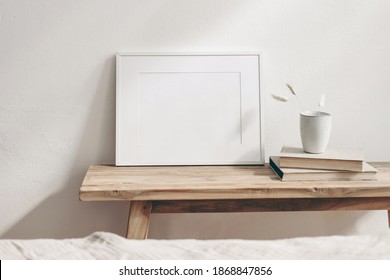 Horizontal white frame mockup on vintage wooden bench, table. Ceramic mug with dry Lagurus ovatus grass and books. White wall background. Scandinavian interior room design. Selective focus. - Shutterstock ID 1868847856