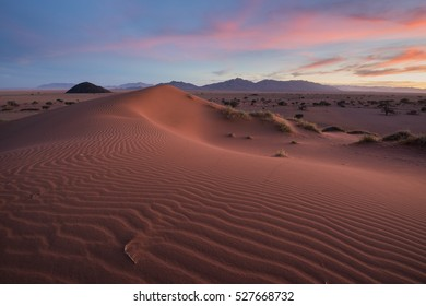 A horizontal wide angle photograph of the rippled red sand dunes during sunset in Namibia