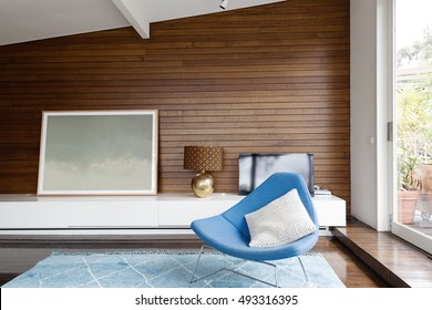 Horizontal wood panelling and blue occasional chair in mid century modern living room