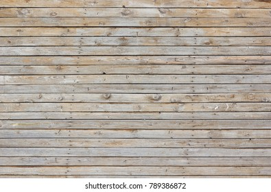 Horizontal wooden gray boards. Empty background of a wide rural wooden fence with iron nails on the surface of the barn.