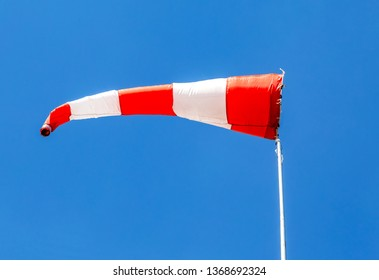 Horizontally flying windsock wind vane with red and white lines against blue sky