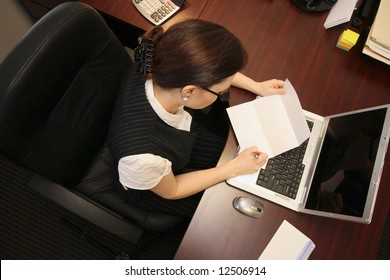 Horizontally framed overhead shot of a businesswoman at her desk reading a letter