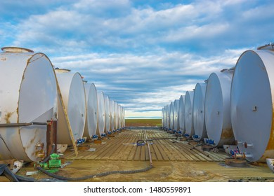 Horizontally located cylindrical tanks with oil products and fuel for equipment. Installed in two rows. Silver gray. Warehouse for the storage of fuel and lubricants.