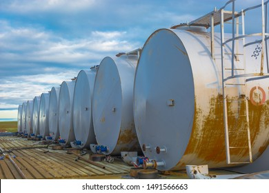 Horizontally located cylindrical tanks with oil products and fuel for equipment.  Silver gray. Warehouse for the storage of fuel and lubricants. At the bottom of the tanks taps for fuel recruitment.