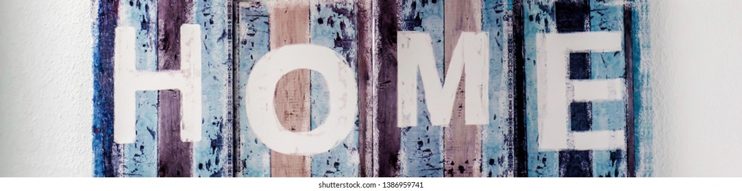 Horizontl view handmade HOME sigh, wooden colorful planks over white wall background. Rustic decor