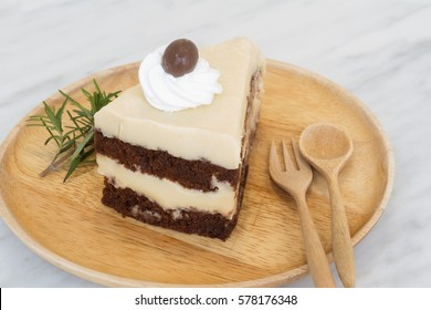 Horlick and Chocolate Cold Layer Cake Decorated by Cream and Top Chocolate Ball on Wooden Plate with Spoon and Fork on Marble Table (Selective Focus)
