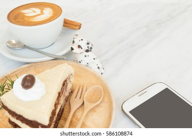 Horlick Cold Layer Cake and Wooden Fork Spoon Plate, Tulip Rosette Latte Art on Top Hot Coffee with Cinnamon on White Ceramic Plate, Cute Puppy Dog Statue and Smart Mobile Phone All on Marble Table