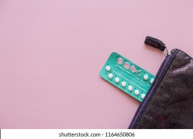 hormonal oral contraceptives in a blister for a month of reception lie on a table on a pink background with free space for text
