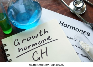 Hormone growth hormone  written on notebook. Test tubes and hormones list.