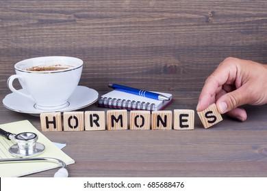 hormones. Wooden letters on dark background