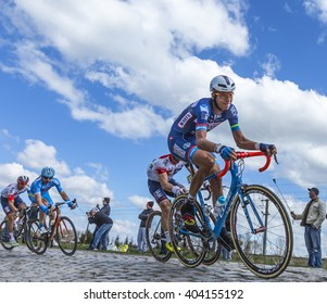 HORNAING,FRANCE-APR 10: Group of cyclists riding in the peloton on a paved road in Hornaing, France during Paris Roubaix on 10 April 2016.
