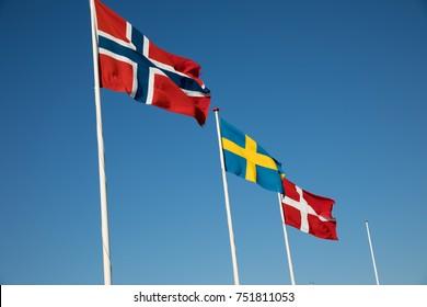 HORNBAEK, ZEALAND, DENMARK - AUGUST 16, 2107: Scandinavian country flags on white flag poles flying in wind against blue sky