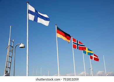 HORNBAEK, ZEALAND, DENMARK - AUGUST 16, 2107: Scandinavian, German and Finnish country flags on white flag poles flying in wind against blue sky