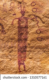 """A horned anthropomorph holding a snake with a bird """"spirit helper"""" pictograph in Barrier Canyon Style stands next to the Head of Sinbad in the San Rafael Swell, Utah, United States."""