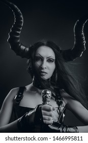 Horned seductive demonic girl posing with sword over dark background