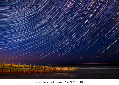 Hornsea Beach on the Yorkshire coast under a beautiful night sky, dramatic long exposure astrophotography showing beautiful stars & star trails