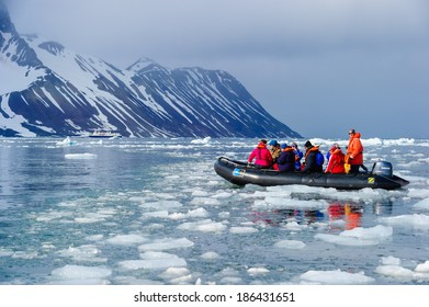 HORNSUND, SVALBARD, NORWAY - JULY 26, 2010: Tourists from the National Geographic Explorer cruise ship on inflatable rafts in the Artic Ocean exploring a fijord in the Arctic.