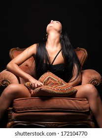 Horny girl pleasing herself sitting on the armchair