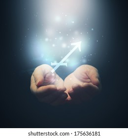 Horoscope Sagittarius sign, female hands opening to light and holding zodiac symbol