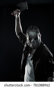 Horrible maniac with bloody chopper posing over dark background