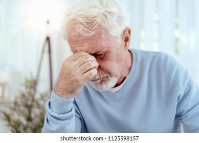 Horrible migraine. Sad senior man touching nose bridge and closing eyes