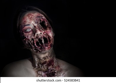 horrible scary zombie girl on black background with copyspace
