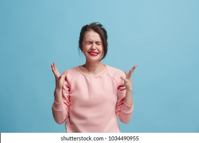 Horrible, stress, shock. Female half-length portrait isolated at blue studio. Young emotional surprised woman clasping head in hands. Human emotions, facial expression concept. Trendy colors. Front