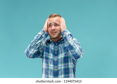 Horrible, stress, shock. Male half-length portrait isolated at blue studio. Young emotional unhappy man clasping head in hands. Human emotions, facial expression concept. Trendy colors