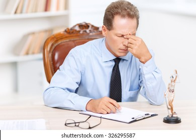 Horribly tired. Professional exhausted Lawyer holding his fingers on the nose and sitting at the table while feeling weary